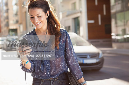 Happy businesswoman using mobile phone while listening music on street Stock Photo - Premium Royalty-Free, Image code: 698-07158776