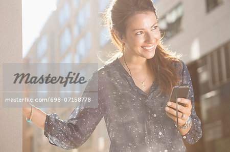 Happy businesswoman looking away while listening music through mobile phone outdoors Stock Photo - Premium Royalty-Free, Image code: 698-07158778