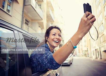 Happy businesswoman photographing through mobile phone from car window on street Stock Photo - Premium Royalty-Free, Image code: 698-07158788