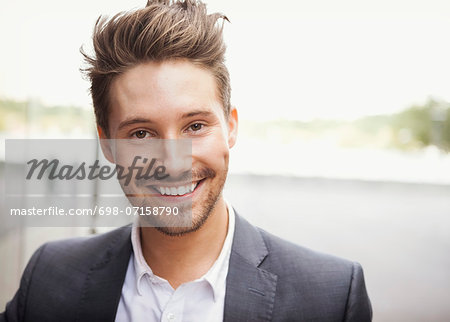 Portrait of happy businessman outdoors Stock Photo - Premium Royalty-Free, Image code: 698-07158790