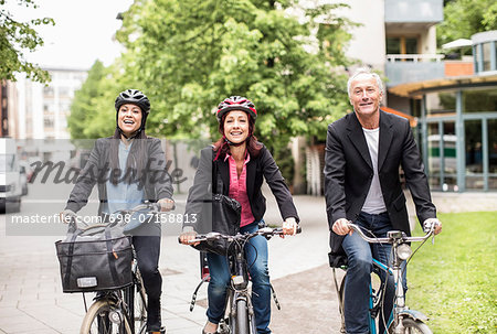 Happy business people riding bicycles on street Stock Photo - Premium Royalty-Free, Image code: 698-07158813