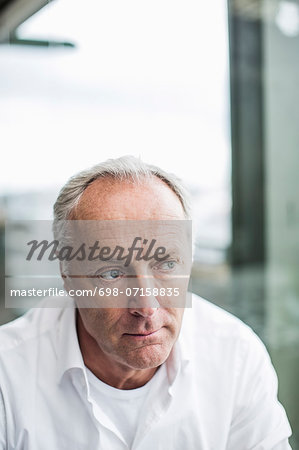 Pensive mature businessman looking away Stock Photo - Premium Royalty-Free, Image code: 698-07158835