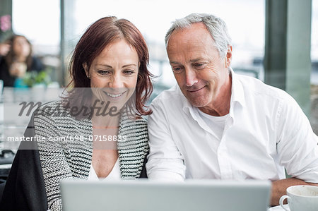 Happy business people using laptop at cafe Stock Photo - Premium Royalty-Free, Image code: 698-07158839