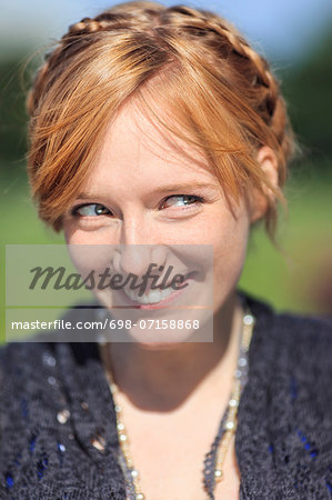 Thoughtful woman smiling in park Stock Photo - Premium Royalty-Free, Image code: 698-07158868