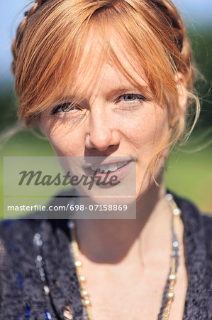 Portrait of redhead woman in park Stock Photo - Premium Royalty-Free, Image code: 698-07158869