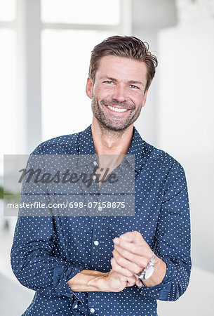 Portrait of happy businessman rolling up shirt sleeves in office Stock Photo - Premium Royalty-Free, Image code: 698-07158875