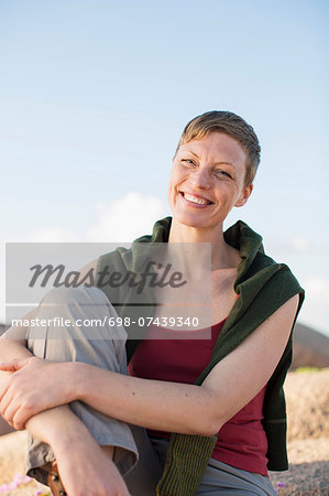 Portrait of happy woman relaxing on rock against clear sky Stock Photo - Premium Royalty-Free, Image code: 698-07439340
