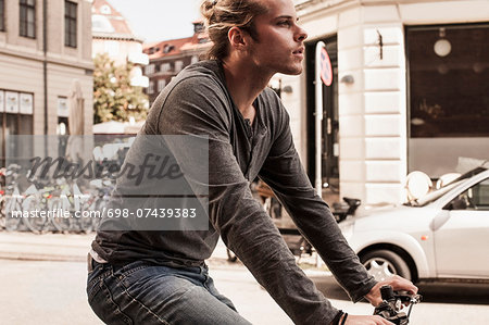 Side view of young man cycling on city street Stock Photo - Premium Royalty-Free, Image code: 698-07439383
