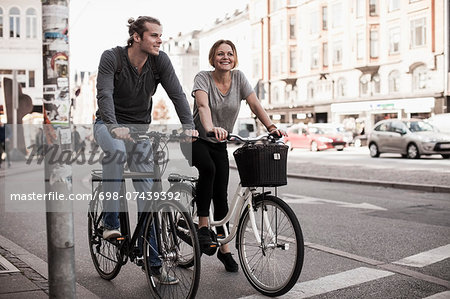 Happy couple riding bicycles on city street Stock Photo - Premium Royalty-Free, Image code: 698-07439392