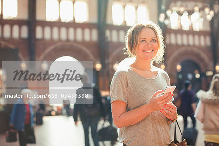 Happy mid adult woman with mobile phone standing on railway station Stock Photo - Premium Royalty-Free, Image code: 698-07439398