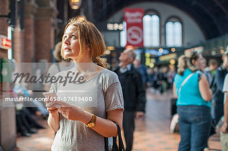 Mid adult woman with mobile phone looking up while standing on railway station Stock Photo - Premium Royalty-Free, Image code: 698-07439400