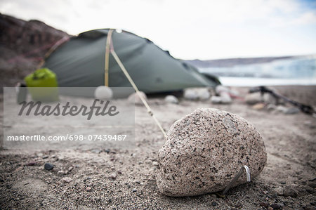 View of stone with camping tent in background Stock Photo - Premium Royalty-Free, Image code: 698-07439487