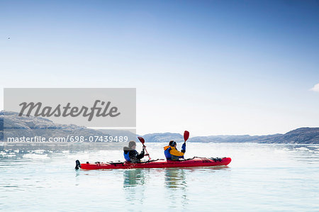 People kayaking on sea against clear sky Stock Photo - Premium Royalty-Free, Image code: 698-07439489