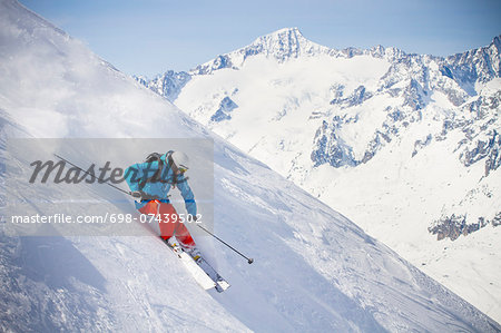 Full length of man skiing on mountain slope Stock Photo - Premium Royalty-Free, Image code: 698-07439502