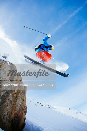 Low angle view of mid adult man skiing against sky Stock Photo - Premium Royalty-Free, Image code: 698-07439503