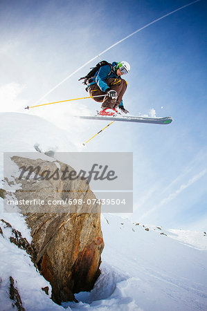 Full length of free ride skier in mid air against sky Stock Photo - Premium Royalty-Free, Image code: 698-07439504