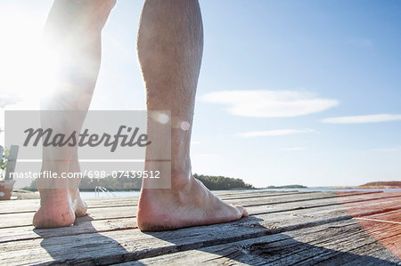 Low section of mature man standing on boardwalk Stock Photo - Premium Royalty-Free, Image code: 698-07439512