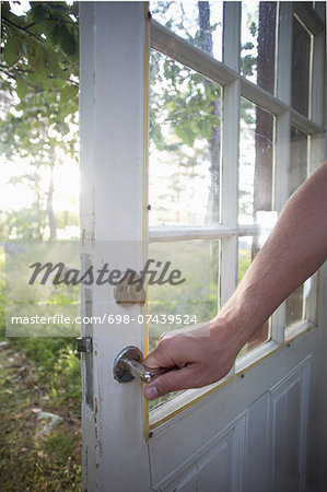 Cropped image of man holding door handle Stock Photo - Premium Royalty-Free, Image code: 698-07439524