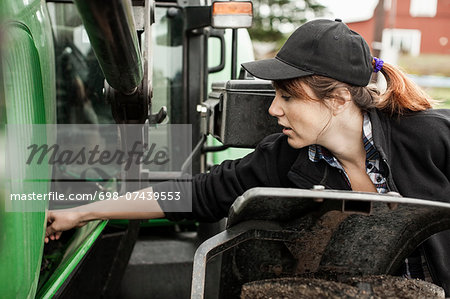 Female farmer repairing tractor Stock Photo - Premium Royalty-Free, Image code: 698-07439553
