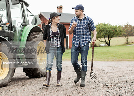 Full length of farming couple walking by tractor Stock Photo - Premium Royalty-Free, Image code: 698-07439557