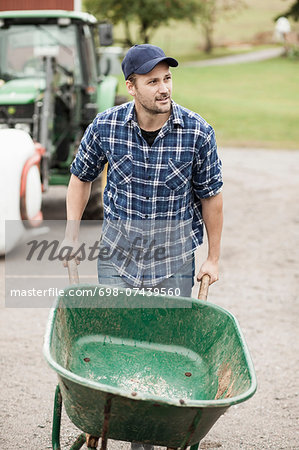 Mid adult farmer pushing wheelbarrow on rural road Stock Photo - Premium Royalty-Free, Image code: 698-07439560