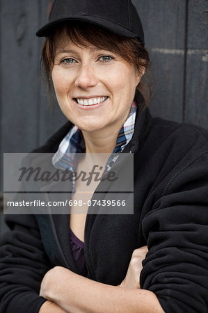 Portrait of happy female farmer standing arms crossed against barn door Stock Photo - Premium Royalty-Free, Image code: 698-07439566