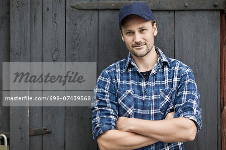 Portrait of confident farmer standing arms crossed against barn door Stock Photo - Premium Royalty-Free, Image code: 698-07439568
