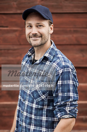 Portrait of confident farmer smiling against barn Stock Photo - Premium Royalty-Free, Image code: 698-07439569