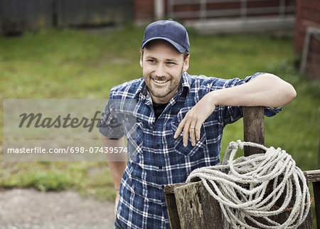 Smiling farmer looking away while leaning on railing at farm Stock Photo - Premium Royalty-Free, Image code: 698-07439574