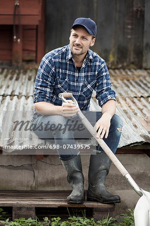 Full length of farmer with shovel sitting on corrugated iron at farm Stock Photo - Premium Royalty-Free, Image code: 698-07439575