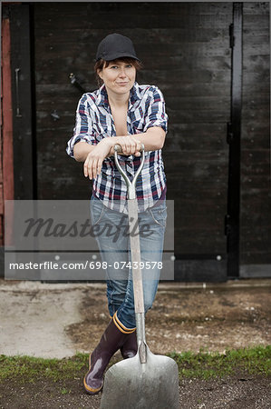 Portrait of confident female farmer with shovel standing against barn Stock Photo - Premium Royalty-Free, Image code: 698-07439578