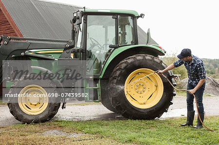 Full length farmer washing tractor wheel with hose in farm Stock Photo - Premium Royalty-Free, Image code: 698-07439582