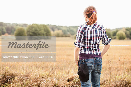 Rear view of female farmer standing at field Stock Photo - Premium Royalty-Free, Image code: 698-07439584