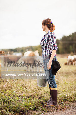 Female farmer with bucket standing on field with animals grazing in background Stock Photo - Premium Royalty-Free, Image code: 698-07439586