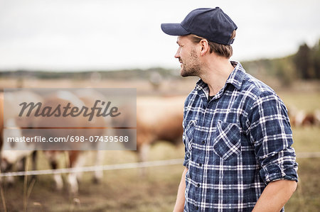 Thoughtful farmer standing on field while animals grazing in background Stock Photo - Premium Royalty-Free, Image code: 698-07439588