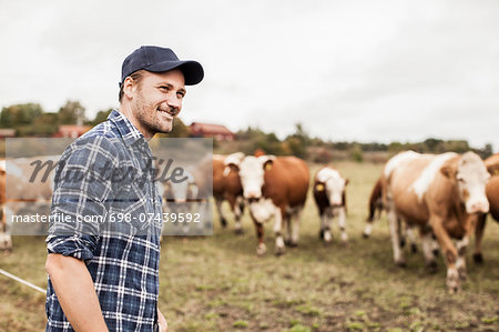 Smiling farmer looking away at field while animals grazing in background Stock Photo - Premium Royalty-Free, Image code: 698-07439592