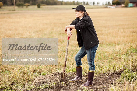Full length of thoughtful woman with pitchfork standing at field Stock Photo - Premium Royalty-Free, Image code: 698-07439594
