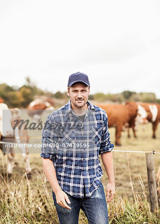 Portrait of confident farmer standing on field while animals grazing in background Stock Photo - Premium Royalty-Free, Image code: 698-07439595
