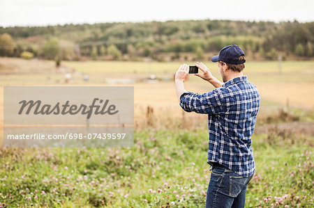 Rear view of farmer photographing field through mobile phone Stock Photo - Premium Royalty-Free, Image code: 698-07439597