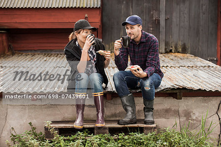 Full length of couple having breakfast on corrugated iron at farm Stock Photo - Premium Royalty-Free, Image code: 698-07439601