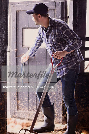 Full length of farmer with pitchfork closing barn door Stock Photo - Premium Royalty-Free, Image code: 698-07439606
