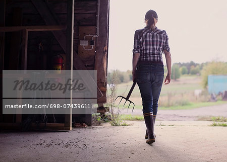 Rear view of female farmer with pitchfork walking in barn Stock Photo - Premium Royalty-Free, Image code: 698-07439611
