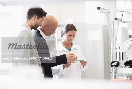 Female engineer and businessmen discussing machine in manufacturing plant Stock Photo - Premium Royalty-Free, Image code: 698-07439615