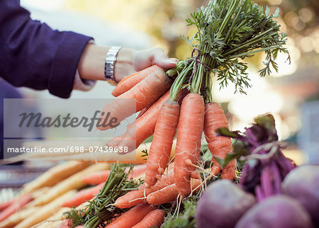 Cropped image of woman buying carrots at market stall Stock Photo - Premium Royalty-Free, Image code: 698-07439638