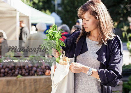 Young woman buying leaf vegetables at market Stock Photo - Premium Royalty-Free, Image code: 698-07439646