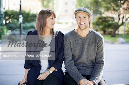 Happy couple sitting outdoors Stock Photo - Premium Royalty-Free, Image code: 698-07439664
