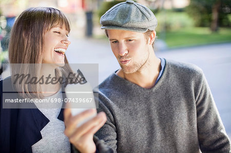 Happy couple photographing themselves through mobile phone outdoors Stock Photo - Premium Royalty-Free, Image code: 698-07439667