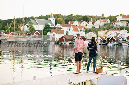 Full length rear view of couple fishing on pier at lake Stock Photo - Premium Royalty-Free, Image code: 698-07439686
