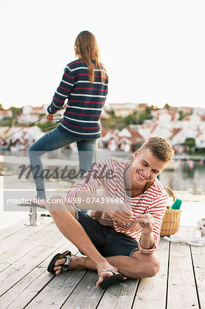 Happy man adjusting fishing rod while woman fishing in background at pier Stock Photo - Premium Royalty-Free, Image code: 698-07439688