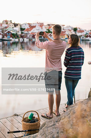 Rear view of couple photographing view through mobile phone by lake Stock Photo - Premium Royalty-Free, Image code: 698-07439689